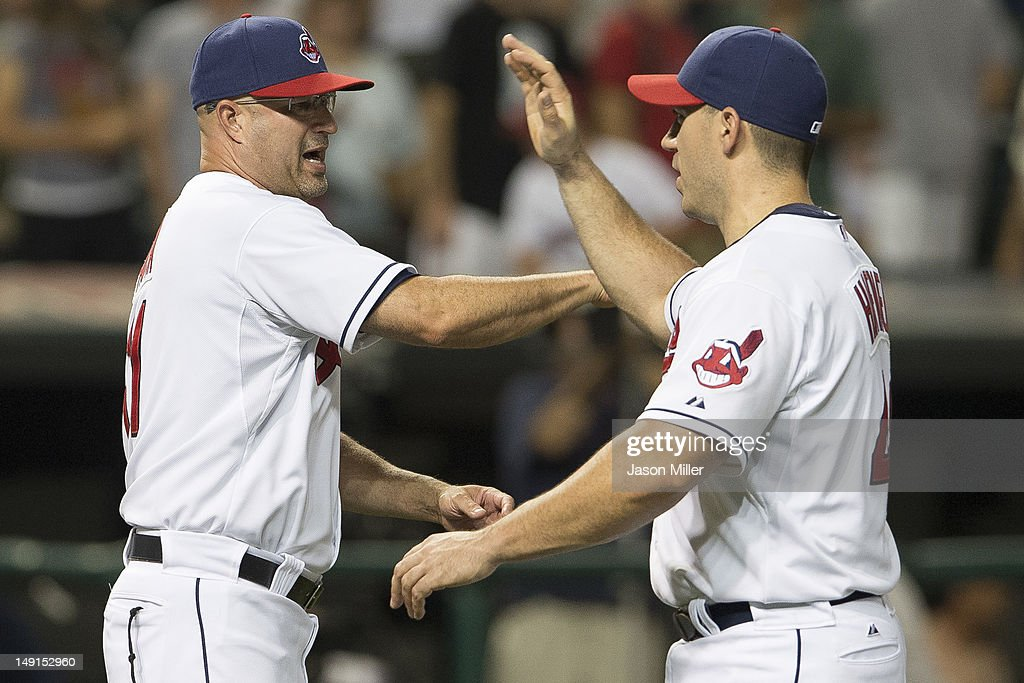 Manager Manny Acta #11 celebrates with Travis Hafner #48 of the Cleveland Indians after the Indians defeated the Baltimore Orioles at Progressive Field on July 23, 2012 in Cleveland, Ohio. The Indians defeated the Orioles 3-1.