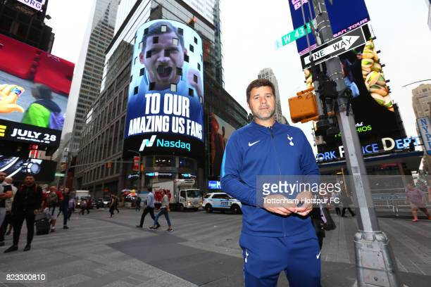 Manager Mauricio Pochettino poses as a Tottenham Hotspur advert plays on a screen in Time Square on July 25 2017 in New York New York