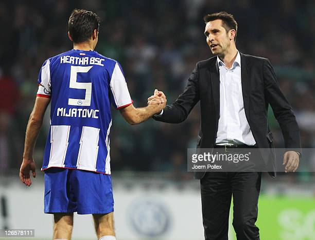 Manager Michael Preetz and Andre Mijatovic of Berlin shake hands after the Bundesliga match between Werder Bremen and Hertha BSC Berlin at Weser...