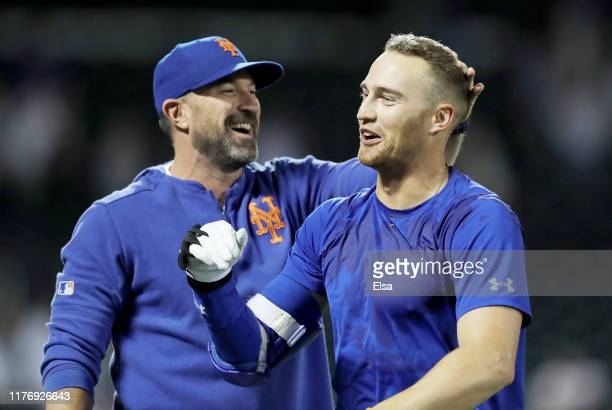 Manager Mickey Callaway of the New York Mets congratulates Brandon Nimmo after Nimmo scored the game winning run on a bases loaded walk at Citi Field...