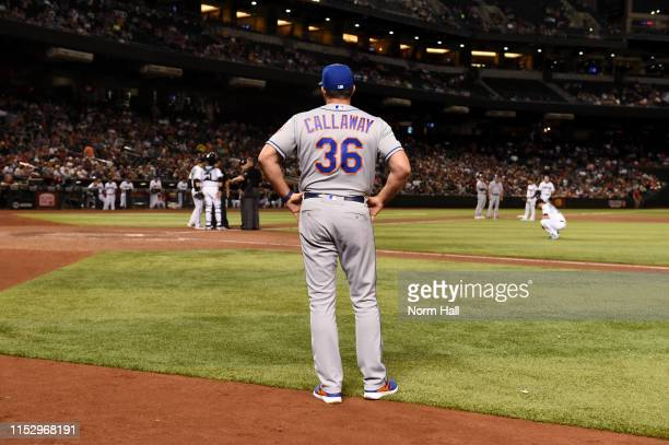 Manager Mickey Callaway of the New York Mets looks on as umpires discuss a ground rule double with manager Torey Lovullo and Alex Avila of the...