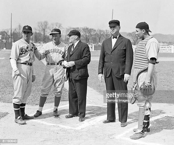 Manager Mickey Cochrane of the Detroit Tigers and manager Bill McKechnie of the Cincinnati Reds review the ground rules with umpires George...