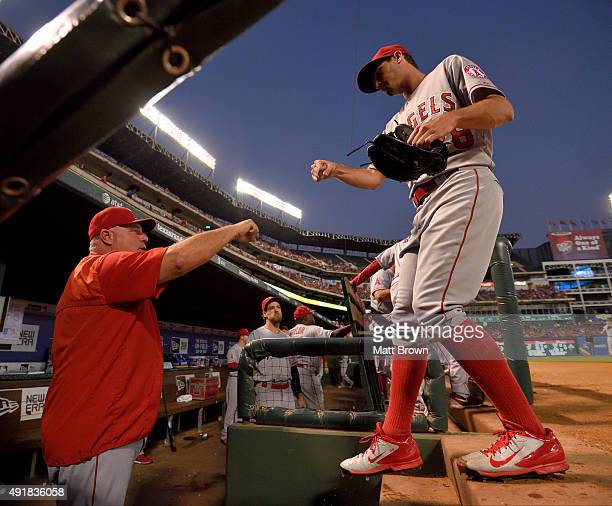 Manager Mike Scioscia and pitcher Andrew Heaney of the Los Angeles Angels of Anaheim fist bump as Heaney returns to the dugout after the first inning...