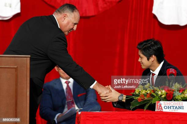 Manager Mike Scioscia and Shohei Ohtani shake hands on stage during the press conference introducing Ohtani to the Los Angeles Angels of Anaheim at...