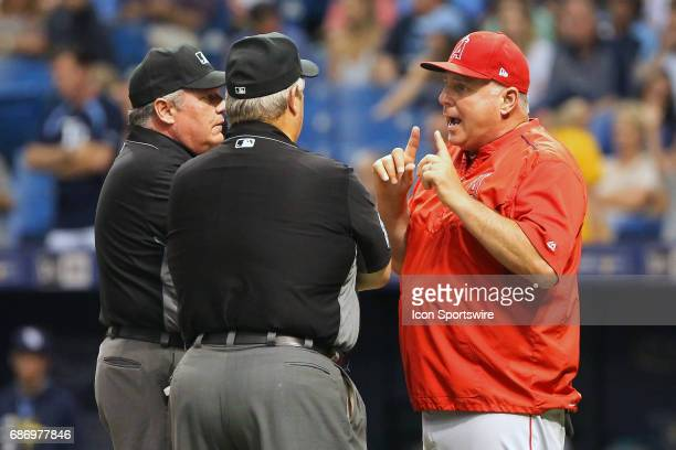 Manager Mike Scioscia has a word with two umpires after the umpire crew called Nolan Fontana of the Angels out at second base during the MLB regular...