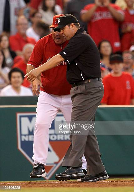 Manager Mike Scioscia of the Los Angeles Angels of Anaheim has a heated argument wih third base umpire Doug Eddings after a foul ball call in the...