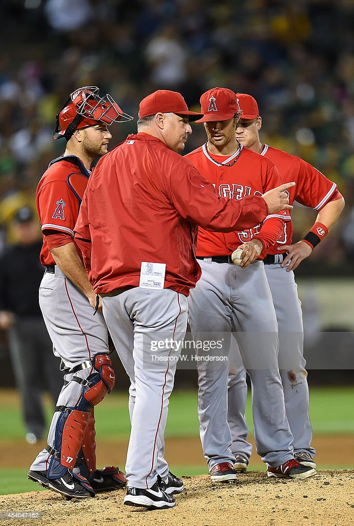 Manager Mike Scioscia #14 of the Los Angeles Angels of Anaheim signals the bullpen to make a pitching change taking C.J. Wilson #33 out of the game in the bottom of the seventh inning against the Oakland Athletics at O.co Coliseum on August 23, 2014 in Oakland, California.