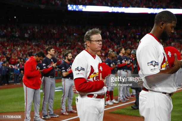 Manager Mike Shildt and Dexter Fowler of the St Louis Cardinals look on during the singing of the national anthem prior to Game 1 of the NLCS between...
