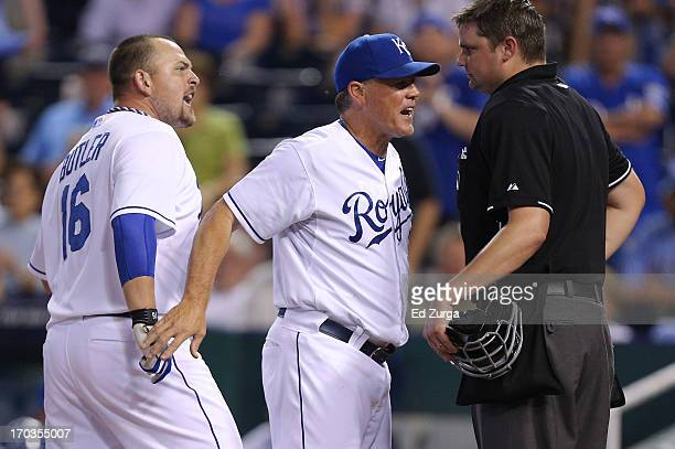 Manager Ned Yost of the Kansas City Royals gets between Billy Butler and plate umpire Jordan Baker after Butler was ejected for arguing strike calls...