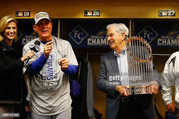 Manager Ned Yost of the Kansas City Royals left reacts as Kansas City Royals owner David D Glass holds the Commissioner's Trophy after the Kansas...