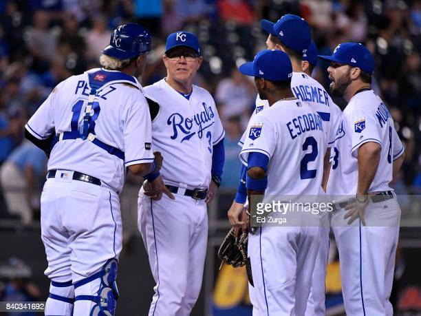 Manager Ned Yost of the Kansas City Royals talks to members of his team during a pitching change against the Tampa Bay Rays in the sixth inning at...