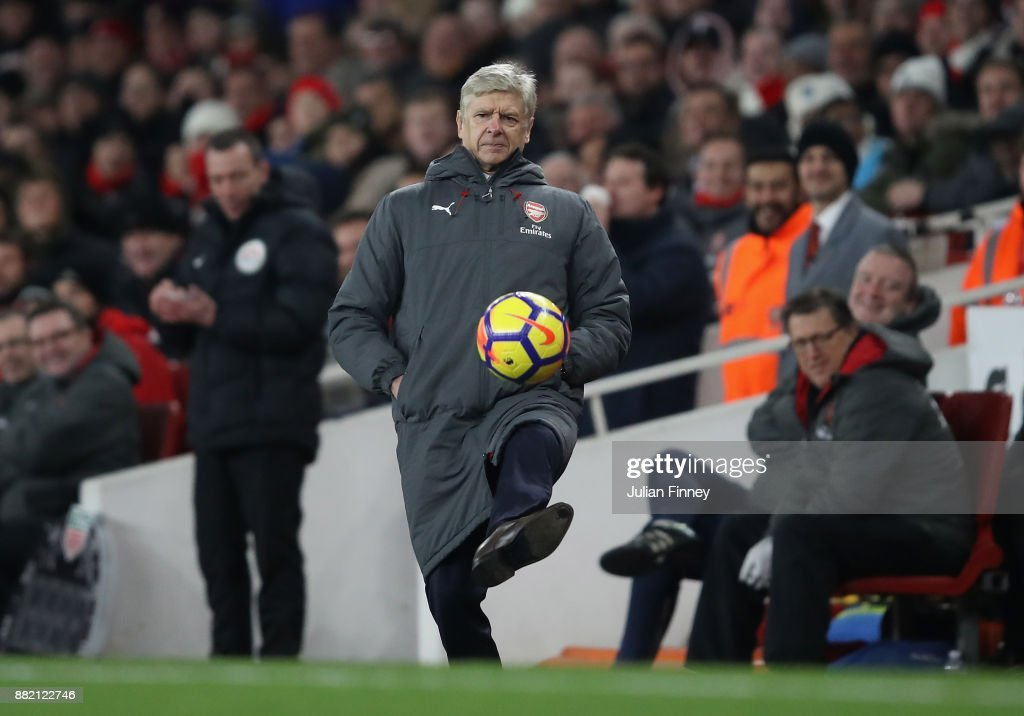 Manager of Arsenal Arsene Wenger kicks the ball back during the Premier League match between Arsenal and Huddersfield Town at Emirates Stadium on November 29, 2017 in London, England.