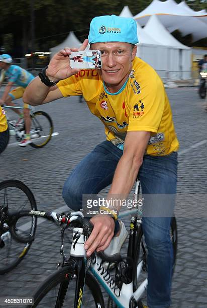 Manager of Astana Pro Team Alexander Vinokourov holds his cellphone with a picture of Vincenzo Nibali on it during the lap of honor, following the...