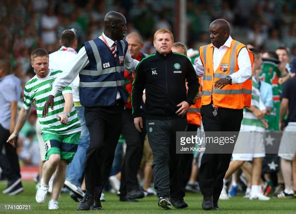 Manager of Celtic Neil Lennon is escorted off the pitch as traveling fans invade the pitch during a pre season friendly match between Brentford and...