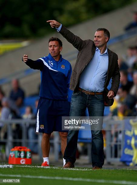 Manager of Dagenham Redbridge Wayne Burnett and first team coach Darren Currie urge on their side during the Sky Bet League Two match between Oxford...