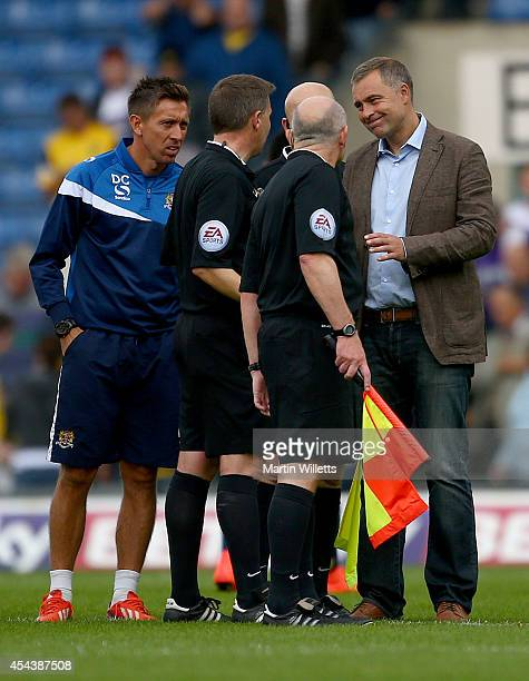 Manager of Dagenham Redbridge Wayne Burnett and first team coach Darren Currie talk with referee Gary Sutton and his assistants after the Sky Bet...