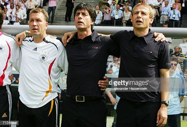 Manager of Germany Juergen Klinsmann sings his national anthem with his coaching staff Andreas Kopke and Joachim Low prior to the FIFA World Cup...