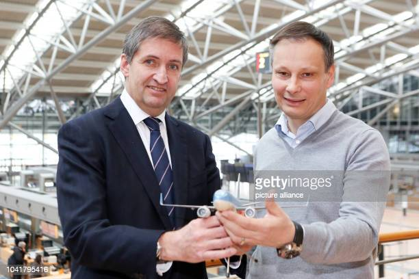 Manager of Hamburg Airport Michael Eggenschwilller and CEOof TUIGermany Christian Clemens hold a model Boeing 737800 plane as part of a press...