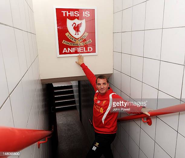 Manager of Liverpool Brendan Rodgers with the original 'This Is Anfield' sign after it was remounted at Anfield on July 9 2012 in Liverpool England