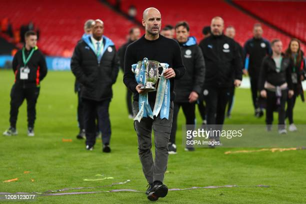 Manager of Manchester City Pep Guardiola holds the trophy after the Carabao Cup Final match between Aston Villa and Manchester City at Wembley Stadium