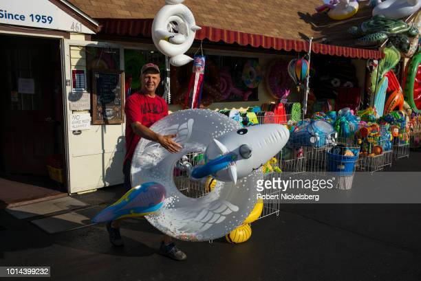 Manager of Seaberry Surf carries a float to a display area July 31, 2018 in Wellfleet, Massachusetts. Started in 1962, Seaberry Surf is one of Cape...