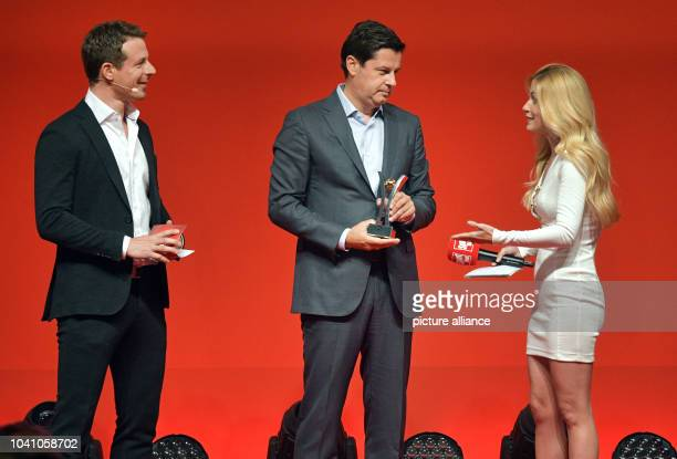Manager of the DFL Christian Seifert stands on stage with presenters Alexander Bommes und Andrea Kaiser at the Sport BildAward ceremony in Hamburg...