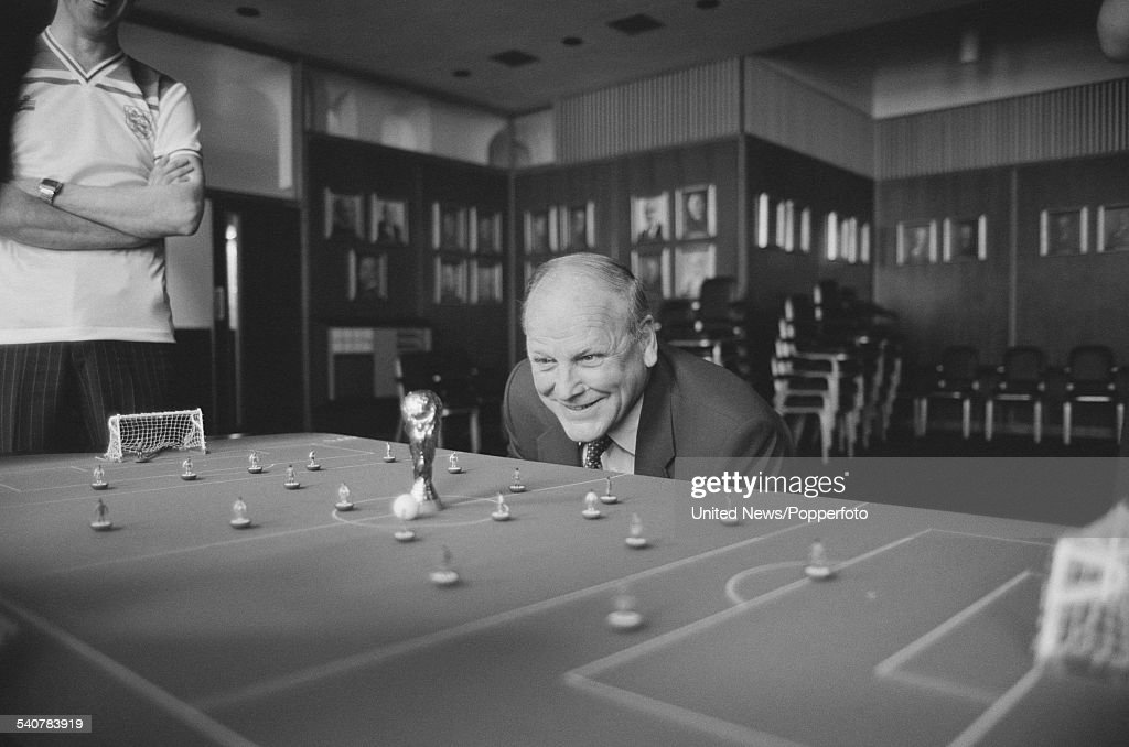 Manager of the England football team, Ron Greenwood (1921-2006) views a replica of the World Cup trophy placed in the centre spot of a subbuteo table in London on 4th May 1982.