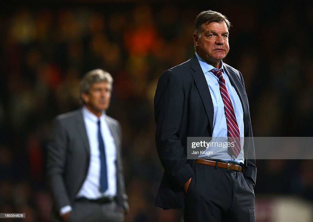 Manager of West Ham United Sam Allardyce (R) and Manager of Manchester City Manuel Pellegrini look on during the Barclays Premier League match between West Ham United and Manchester City at the Boleyn Ground on October 19, 2013 in London, England.