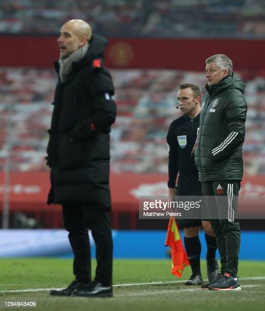 Manager Ole Gunnar Solskjaer of Manchester United and Manager Pep Guardiola of Manchester City watch from the touchline during the Carabao Cup Semi...