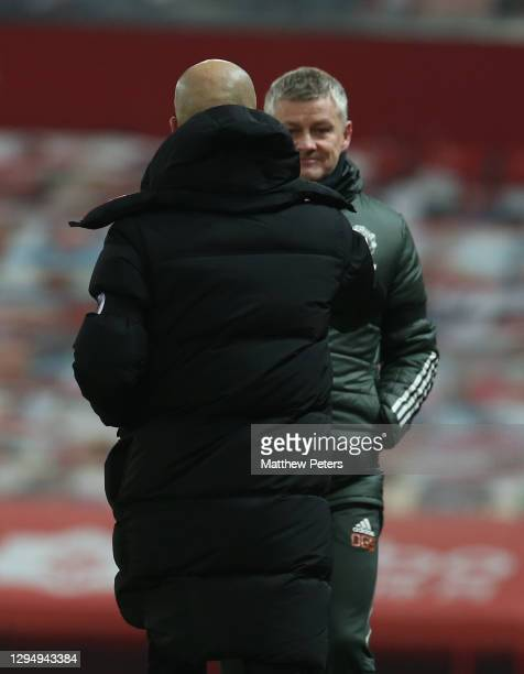 Manager Ole Gunnar Solskjaer of Manchester United talks to Manager Pep Guardiola of Manchester City after the Carabao Cup Semi Final between...