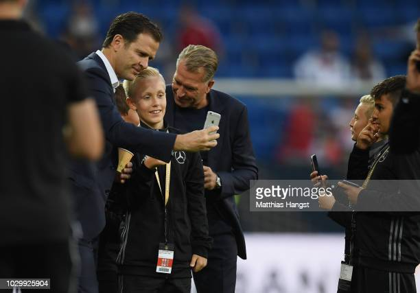 Manager Oliver Bierhoff and goalkeeper coach Andreas Koepke take photos with escort kids prior to the International Friendly match between Germany...