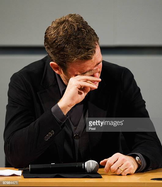 Manager Oliver Bierhoff wipes away his tears during the press conference of the German national football team due to the death of Robert Enke at the...