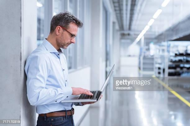 manager on shop floor of factory using laptop - halle gebäude stock-fotos und bilder