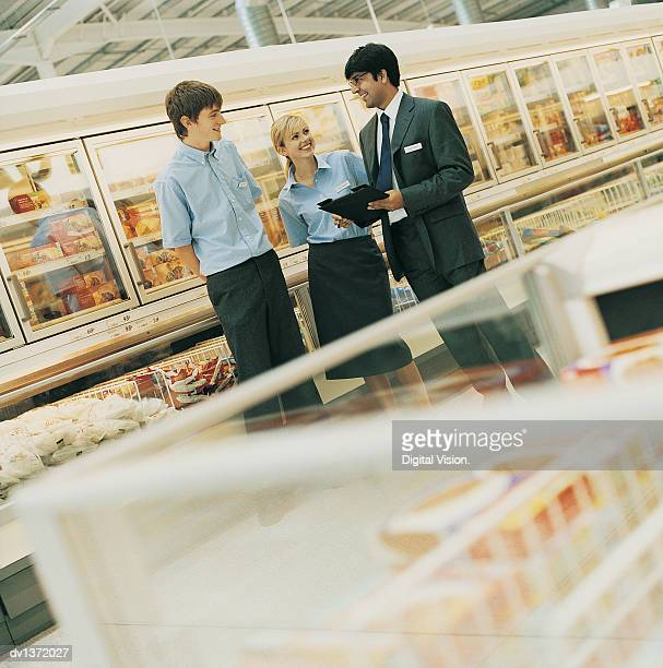 Manager Organising His Shop Assistants in the Frozen Food Aisle of a Supermarket