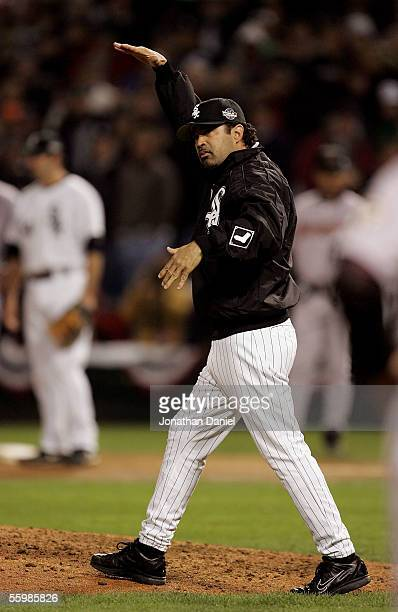 Manager Ozzie Guillen of the Chicago White Sox gestures for the big and tall pitcher Bobby Jenks as he makes a pitching change in the eighth inning...
