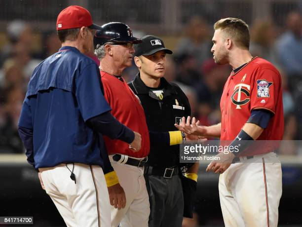 Manager Paul Molitor and third base coach Gene Glynn of the Minnesota Twins get between home plate umpire Mark Wegner and Brian Dozier after a strike...