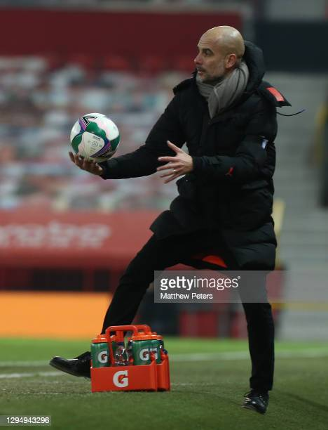 Manager Pep Guardiola of Manchester City catches the ball during the Carabao Cup Semi Final between Manchester United and Manchester City at Old...