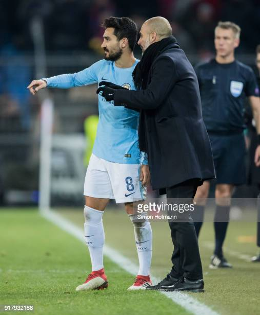 Manager Pep Guardiola of Manchester City gives directoons to Ilkay Gundogan during the UEFA Champions League Round of 16 First Leg match between FC...