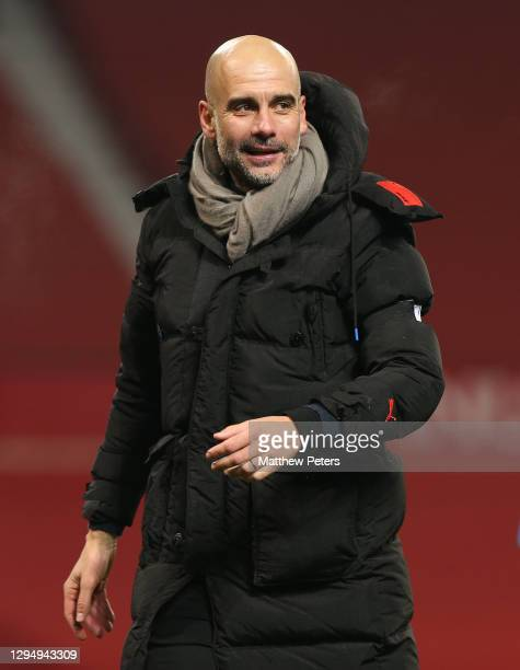 Manager Pep Guardiola of Manchester City walks off after the Carabao Cup Semi Final between Manchester United and Manchester City at Old Trafford on...