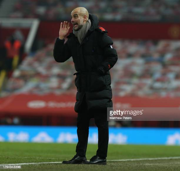 Manager Pep Guardiola of Manchester City watches from the touchline during the Carabao Cup Semi Final between Manchester United and Manchester City...