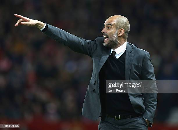 Manager Pep Guardiola of Manchester City watches from the touchline the EFL Cup Fourth Round match between Manchester United and Manchester City at...