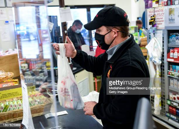 Manager Pete Ostrowski hands a customer a bag of groceries around the plexiglass partition at the Redner's Quick Shoppe on Tuckerton Road in...
