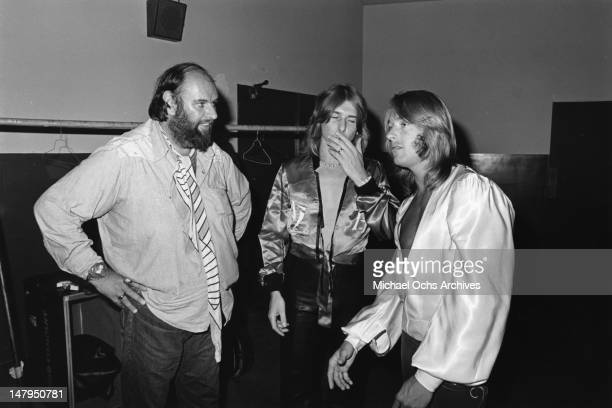 Manager Peter Grant and musicians Mick Ralphs and Simon Kirke of the rock and roll band 'Bad Company' backstage in circa 1976