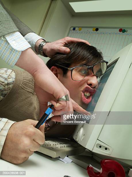 Manager pushing office worker's face against computer screen