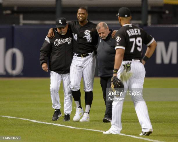 Manager Rick Renteria and head trainer Brian Ball help Eloy Jimenez of the Chicago White Sox off the field after Jimenez suffered a high ankle strain...