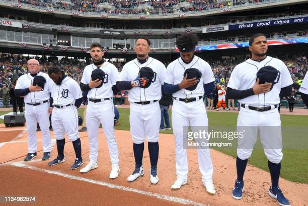 Manager Ron Gardenhire of the Detroit Tigers and a group of his players stand together on the field during the National Anthem prior to the Opening...