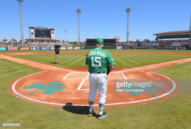 Manager Ron Gardenhire of the Detroit Tigers stands at home plate wearing a green jersey and hat to honor St Patricks Day prior to the Spring...