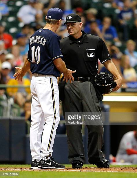 Manager Ron Roenicke of the Milwaukee Brewers argues with umpire Ed Hickox after he called Jean Segura of the Brewers out for getting hit by his bunt...