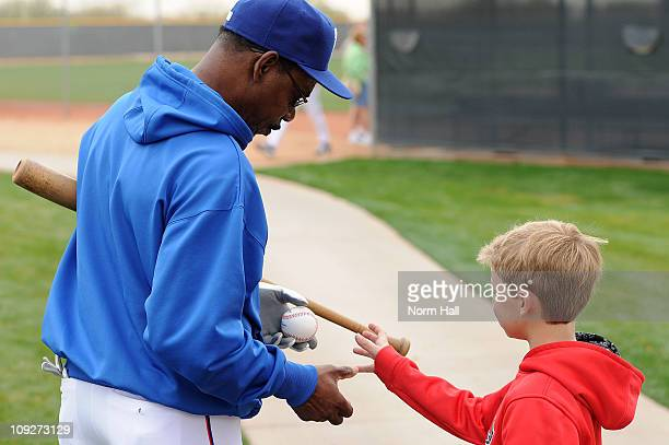 Manager Ron Washington of the Texas Rangers signs an autograph for a young fan at Surprise Stadium on February 18 2011 in Surprise Arizona