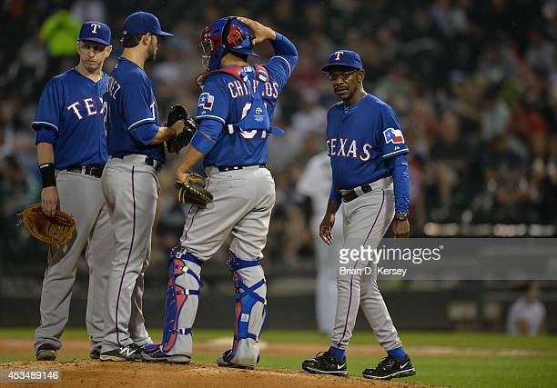 Manager Ron Washington of the Texas Rangers walks out to the mound to take starting pitcher Nick Martinez out of the game as he stands on the mound...